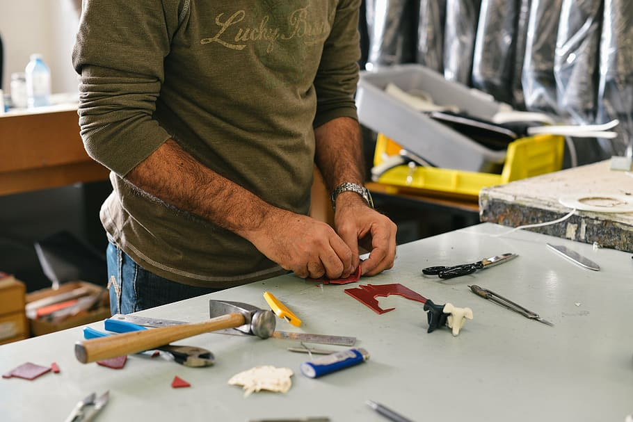 Pictured: a worker at a work table using tools