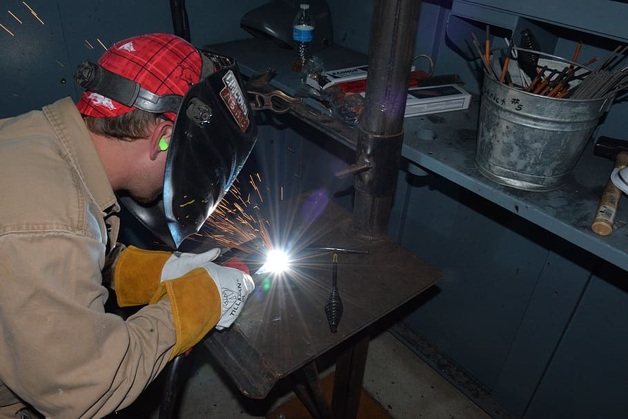 A construction boilermaker welding metal with a tool